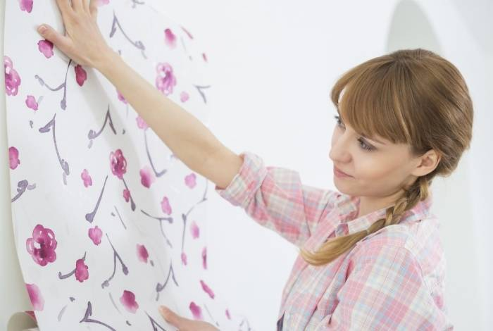 Поклейка бумажных обоев на стену девушкой