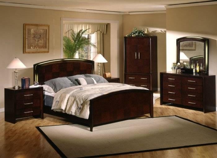 Спальня с темной мебелью и светлыми обоями