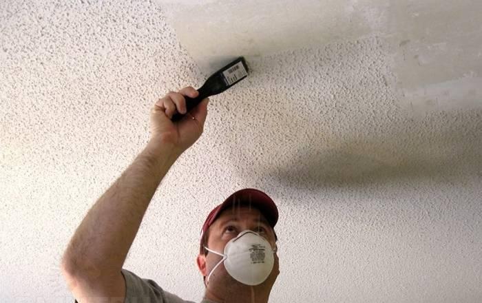 Мастер счищает с потолка известку