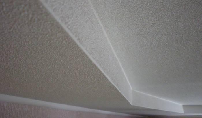 Многоуровневый потолок в комнате, оклеенный и окрашенный